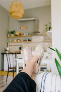woman kicking her feet back on the couch